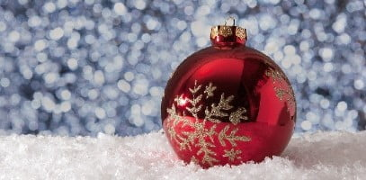 red christmas bauble on snow with festive glitter backdrop