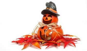 halloween pumpkin with hat sitting on autumn leaves