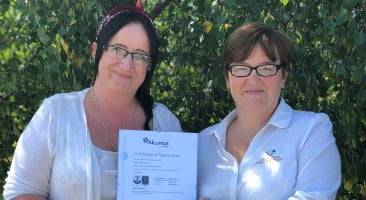 grotech staff holding the latest ISO certificate