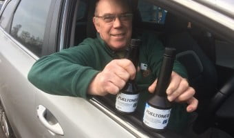 Martin Usher, Grotech MD sitting in a car holding bottles of fueltone