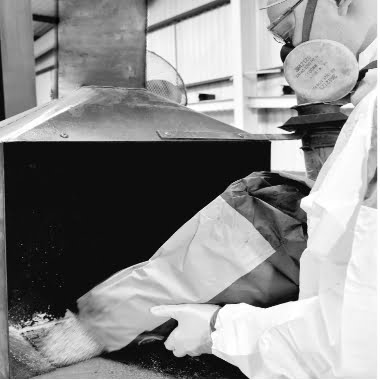 grotech staff member emptying powder into mixing machine in factory