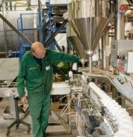 member of grotech staff inspecting bottles on filling line
