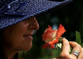 lady in hat smelling a rose