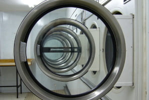 row of washing machine doors in commercial launderette